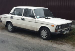 A picture of an old white lada on the side of the road in Kiev, Ukraine
