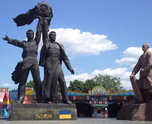 A large statue in Kiev, Ukraine that shows two men holding up an emblem