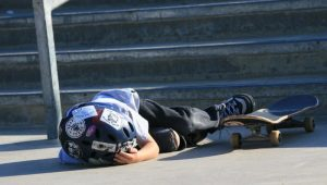 A kid has fallen from his skateboard and can't get up